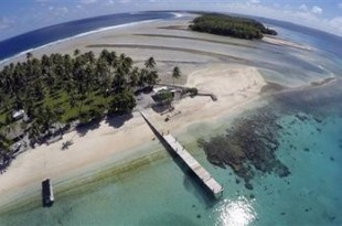 This Nov. 8, 2015 aerial photo shows a small section of the atoll that has slipped beneath the water line only showing a small pile of rocks at low tide on Majuro Atoll in the Marshall Islands. Climate change poses an existential threat to places like the Marshall Islands, which protrude only 6 feet (2 meters) above sea level in most places. (AP Photo/Rob Griffith)