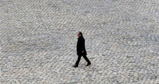 French President Francois Hollande walks in the courtyard of the Invalides national monument during a ceremony in Paris, Friday, Nov. 27, 2015. Intoning the names of 130 dead, a subdued France paid homage Friday to those killed two weeks ago in the attacks that gripped Paris in fear and mourning. (AP Photo/Francois Mori)