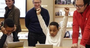 """FILE - In this Wednesday, Dec. 9, 2015, file photo, third-grader Jaysean Erby raises his hands as he solves a coding problem as Apple CEO Tim Cook watches from behind during a coding workshop at an Apple Store, in New York. There's a nationwide push to improve computer literacy in elementary school, and entrepreneurs are jumping aboard. """"You really want kids to learn these building blocks as young as possible and then build on them,"""" said Cook. (AP Photo/Mark Lennihan, File)"""