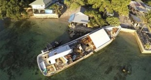 This aerial Nov. 5, 2015, photo shows a boat that wrecked the back of Foreign Minister Tony Du Brum's house on Majuro Atoll in the Marshall Islands, Thursday, Nov. 5, 2015. Climate change poses an existential threat to places like the Marshall Islands, which protrude only 6 feet (2 meters) above sea level in most places. King tides, when the alignment of the Earth, moon and sun combine to produce the most extreme tidal effects, and storm surges cause floods that contaminate fresh water, kill crops, and erode land. As a result, some Marshallese think an exodus as inevitable, while others are planning to stay and fight. (AP Photo/Rob Griffith)