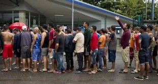 In this Saturday, Nov. 21, 2015 photo, Cuban migrants line up for breakfast given to them by an evangelical church, outside of the border control building in Penas Blancas, Costa Rica, on the border with Nicaragua. Thousands of Cuban migrants have been able to make the trip to the U.S. thanks to a constant flow of information between migrants starting the journey and those who have just completed it. (AP Photo/Esteban Felix)