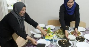 In this photo taken Tuesday, Nov. 10, 2015, Syrian refugees Reem Habashieh, right, and her mother Khawla Kareem, left, prepare dinner in their flat in Zwickau, eastern Germany. Three months after their arrival in Germany and after being bounced around from temporary shelter to temporary shelter, crammed together with hundreds of other refugees, the Syrian family of two boys, two girls and their widowed mother finally has their own four walls to call home. (AP Photo/Jens Meyer)