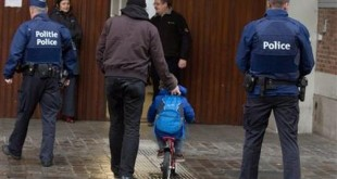 A man wheels a boy on his bicycle past police officers as they arrive for school in the center of Brussels on Wednesday, Nov. 25, 2015. Students in Brussels have begun returning to class after a two-day shutdown over fears that a series of simultaneous attacks could be launched around the Belgian capital. (AP Photo/Virginia Mayo)