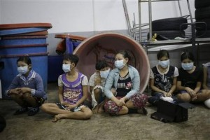 In this Monday, Nov. 9, 2015 photo, children and teenagers sit together to be registered by officials during a raid on a shrimp shed in Samut Sakhon, Thailand. Abuse is common in Samut Sakhon, which attracts workers from some of the world's poorest countries, mostly from Myanmar. An International Labor Organization report estimated 10,000 migrant children aged 13 to 15 work in the city. Another U.N. agency study found nearly 60 percent of Burmese laborers toiling in its seafood processing industry were victims of forced labor. (AP Photo/Dita Alangkara)