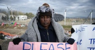 A woman holds a placard as stranded migrants from Somalia protest in front of the border fence, demanding to cross the Greek-Macedonian border near the northern Greek village of Idomeni, Wednesday, Dec. 2, 2015. Hundreds of migrants are stranded on the Greek side, as dozens of them decided to go back in Athens, after Macedonia blocked access to citizens of countries that are not being fast-tracked for asylum in the European Union. (AP Photo/Giannis Papanikos)