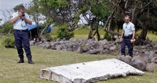FILE - In this July 29, 2015 file photo, French police officers look over a piece of debris from a plane in Saint-Andre, Reunion Island. The wing was later found to be from missing Malaysia Airlines Flight 370 that went missing March 8, 2014, with 239 people aboard while flying from Kuala Lumpur to Beijing. Australian authorities said Thursday, Dec. 3, 2015 new analysis confirms they've likely been searching in the right place for a missing Malaysian airliner. (AP Photo/Lucas Marie,File)