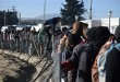 People wait to receive food provided by charities as a man climbs a fence at a refugee camp, near the northern Greek village of Idomeni, Tuesday, Dec. 8, 2015. Macedonian authorities allow only refugees from Syria, Afghanistan and Iraq to cross their country as Greek police says about 1,400 migrants from other nationalities are stuck at the Greek-Macedonian border, sleeping in a shelter provided by charities, in hundreds of tents or in the fields. (AP Photo/Giannis Papanikos)