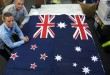 In this March 3, 2014, file photo, Victor Gizzi, left, and David Moginie, managers at flag manufacturer Flagmakers, pose next to flags of New Zealand, left, and Australia, in their factory near Wellington, New Zealand. New Zealanders have chosen a design for a possible new national flag with preliminary results from a postal ballot announced Friday, Dec. 11, 2015, with the results too close to call between two flags featuring the country's iconic silver fern sitting next to the stars that make up the Southern Cross constellation, but using different colors. The winner will be announced Tuesday once all votes are counted. The flag will then be pitted head-to-head against the current flag in a second vote to be held in March 2016. (AP Photo/Nick Perry, File)