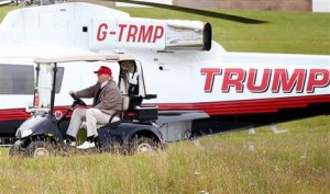 File - In this Friday, July 31, 2015 file photograph, U.S. presidential contender Donald Trump drives his golf buggy past his helicopter during the second day of the Women's British Open golf championship on his Turnberry golf course in Turnberry, Scotland. Britain's Supreme Court Wednesday Dec. 16, 2015, ruled unanimously against tycoon and U.S. presidential contender Donald Trump in his pitched battle to stop the construction of an offshore wind farm near his upscale Scottish golf resort. (AP Photo/Scott Heppell-File)