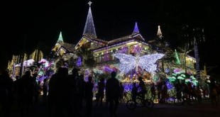 In this Sunday, Nov. 29, 2015 photo, visitors gather around a house lit by thousands of Christmas lights in Cainta, Rizal province, east of Manila, Philippines. The house is drawing huge crowds, especially during weekends, with visitors using the bright lights and festive Christmas decors as their backdrop for selfies with families and friends. (AP Photo/Aaron Favila)