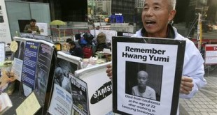 In this Oct. 23, 2015 photo, Hwang Sang-gi, a founding member of advocacy group Banolim, holds a picture of his daughter Yu-mi during an interview denouncing Samsung's response in its latest negotiations with sick workers outside Samsung buildings in Seoul, South Korea. Yu-mi's death from leukemia in 2007 galvanized concern about conditions at Samsung factories and South Korea's semiconductor industry in general. Samsung's hopes of ending years of acrimony and bad publicity over whether its semiconductor factories caused cancer have hit a hitch: some sickened workers and their families say they'll never accept its highly conditional offer of financial assistance. (AP Photo/Ahn Young-joon)