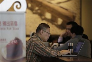 FILE - In this Feb. 16, 2015 file photo, a man surfs Internet on his laptop computer at a Starbuck cafe in Beijing. Chinese President Xi Jinping called Wednesday, Dec. 16 for governments to cooperate in regulating Internet use, stepping up efforts to promote controls that activists complain stifle free expression. (AP Photo/Andy Wong, File)