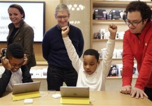 "FILE - In this Wednesday, Dec. 9, 2015, file photo, third-grader Jaysean Erby raises his hands as he solves a coding problem as Apple CEO Tim Cook watches from behind during a coding workshop at an Apple Store, in New York. There's a nationwide push to improve computer literacy in elementary school, and entrepreneurs are jumping aboard. ""You really want kids to learn these building blocks as young as possible and then build on them,"" said Cook. (AP Photo/Mark Lennihan, File)"