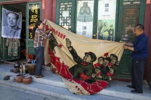 """Vendors unfurl a banner from 1969 depicting former Chinese leader Mao Zedong as he """"inspects the great army of the Cultural Revolution"""" and the slogan """"Navigating the seas depends on the helmsman"""" at a curio market in Beijing, China, Monday, May 16, 2016. Exactly 50 years ago, China embarked on what was formally known as the Great Proletarian Cultural Revolution, a decade of tumult launched by Mao Zedong to revive communist goals and enforce a radical egalitarianism. The milestone was largely ignored Monday in the Chinese media, reflecting continuing sensitivities about a period that was later declared a """"catastrophe."""" (AP Photo/Ng Han Guan)"""